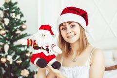 Jultomtenflicka med en leksak Arkivfoto