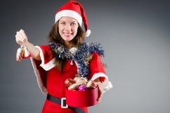 Jultomtenflicka med leksaker på vit Arkivfoto