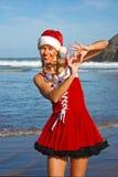 Jultomtenflicka på stranden Royaltyfria Foton