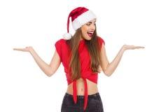 Jultomtenflicka som framlägger produkten Royaltyfri Foto