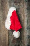Jultomtenhatt som hänger på ladugårdväggen Arkivbild