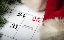 Jultomtenhatt som lägger på en julkalender Arkivfoto
