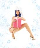 Jultomtenhjälpredaflicka på höga häl med snöflingor #3 arkivbild