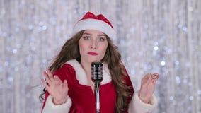 Jultomtenkvinnaallsånger i en retro mikrofon bakgrundsbokehmusik bemärker tematiskt close upp stock video