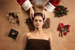 Jultomtenmassören gör SPA behandling för ung härlig kvinna arkivfoton