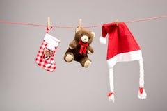 Jultomtenpåsar, nallebjörn och santa hatt på en klädstreck Arkivbilder