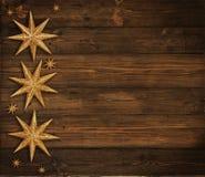 Julträbakgrund, guld- stjärnagarnering, brunt trä Royaltyfri Fotografi