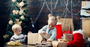 Julungar - lyckabegrepp Barng?va Gulligt litet barn n?ra julgranen St?endeunge med g?van p? royaltyfria bilder