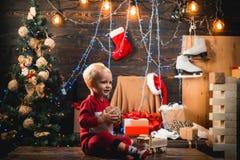 Julungar - lyckabegrepp Den gulliga flickan f?r det lilla barnet dekorerar julgranen inomhus gulliga ungar little royaltyfri bild
