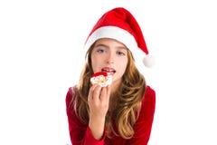 Julungeflicka som äter Xmas-jultomtenkakan royaltyfria bilder