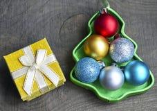 Juluppsättning av färgrika skinande bollar inom av den formade asken för julträd och fiftasken på gammal träbakgrund Juldecorati Royaltyfri Bild