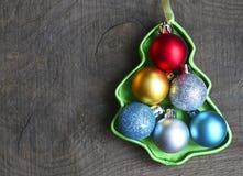 Juluppsättningen av färgrika skinande bollar inom av julträd formade asken på gammal träbakgrund julen dekorerar nya home idéer f Royaltyfri Fotografi