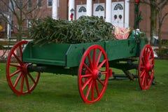 Julvagn som är röd och som är grön i stadfyrkant Arkivfoto