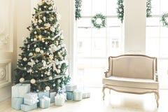 Julvardagsrum med en spis, soffan, julgranen, gåvor och ett stort fönster Härlig dekorerad klassiker för nytt år Arkivbilder