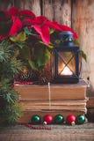 Julvykort med julstjärnan på de gamla böckerna med granträdet, kottar och leksakbollar och brinnande lykta Arkivfoto