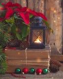 Julvykort med julstjärnan på de gamla böckerna med granträdet, kottar och leksakbollar och brinnande lykta Arkivbild