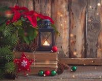 Julvykort med julstjärnan på de gamla böckerna med granträdet, kottar och leksakbollar och brinnande lykta Arkivbilder