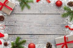 JulXmas-bakgrund med kopieringsutrymme för text Julgran förgrena sig, giftse, klubban, jultomtenhatten, pinecones och snöflingor royaltyfria bilder