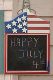 July 4 board 1. Patriotic chalk board with the message happy july 4 written in chalk hanging on a wooden house Stock Photo