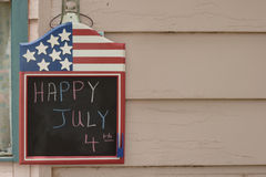 July 4 board 2. Patriotic chalk board with the message happy july 4 written in chalk hanging on a wooden house Royalty Free Stock Images