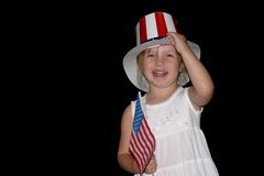July 4th Girl. Cute, young girl holding an American flag and wearing a celebration hat Royalty Free Stock Images
