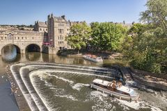 Pulteney Bridge and Weir Bath Somerset UK. 5 July 2017: Bath, Somerset, England, UK - Pleasure Boats at Pulteney Wear on the River Avon Royalty Free Stock Images