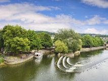 Bath Somerset Pulteney Weir. 8 July 2017: Bath, Somerset, England, UK - Pulteney Weir, one of the attractions of the city, and a pleasure boat moored nearby Royalty Free Stock Photos