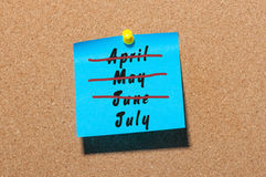 July beginning concept. Sticker with crossed out months April, May and June. Message at business corkboard Royalty Free Stock Photos