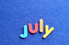 July on a blue background Stock Photos