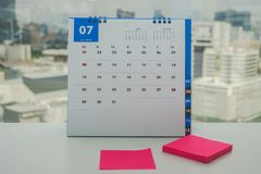 July calendar with pink mock up postit for leaving message to remind meeting and appointment royalty free stock photography