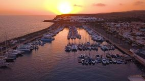 July 10, 2018. Docks, Gran Canaria, Spain. Aerial view of the docks with many yachts during sunset time. Small boats are docked by the coastline on the island stock video