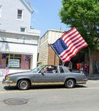 July Fourth Parade in Ridgefield Park, NJ - Car in Parade with Huge American Flag attached on Main Street