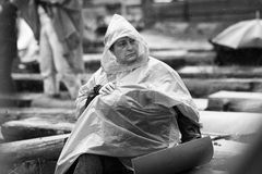 11 JULY 2013 - GARANA, ROMANIA. Scenes and people sitting or walking on the street in a rainy day Stock Photo