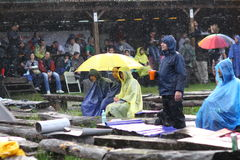 11 JULY 2013 - GARANA, ROMANIA. Scenes and people sitting or walking on the street in a rainy day Royalty Free Stock Photography