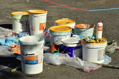 A lot of jars and buckets with paint on the asphalt. Work process on improvement. July 31, 2018. Krasnoyarsk. Russia. a lot of jars and buckets with paint on royalty free stock images