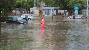JULY 20 2016 MINSK, BELARUS broken cars are on the road after flood with sound. Road worker in overalls. Standing amidst the water stock video