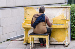July 26, 2014 - Montreal, Canada: Homeless man playing a piano on a street in Montreal, Quebec, Canada. Royalty Free Stock Image