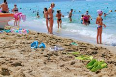 July, 2017 - 5 pairs of beach slippers lie on the sand near the sea. In the background, people are swimming. Alanya, Turkey.  Royalty Free Stock Photography