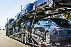 July 4, 2019 Redwood City / CA / USA - Car transporter carries Tesla Model 3 new vehicles along the highway in San Francisco bay royalty free stock images