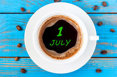 July 1st. Day of the month 1 , everyday calendar written on morning coffee cup at blue wooden background. Summer concept. Top view Royalty Free Stock Images