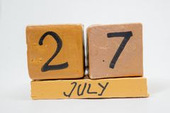 July 27th. Day 27 of month, handmade wood calendar isolated on white background. summer month, day of the year concept. July 27th. Day 27 of month, handmade wood royalty free stock photo