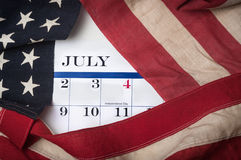 July 4th Flag. Vintage American flag lying next to a calendar with July 4th showing Royalty Free Stock Images