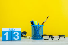 July 13th. Image of july 13, calendar on yellow background with office supplies. Summer time. With empty space for text Royalty Free Stock Photography