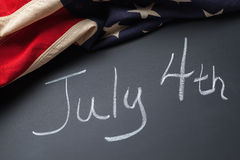 July 4th Sign. Written on a chalkboard with vintage American flag Royalty Free Stock Images