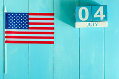 July 4th wooden color calendar with Stars and Stripes flag on blue background. Summer day. Empty space for text Stock Images