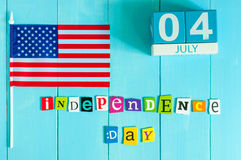 July 4th wooden color calendar with Stars and Stripes flag on blue background. Summer day. Empty space for text Royalty Free Stock Image