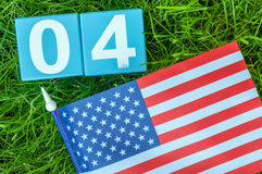 July 4th wooden color calendar with Stars and Stripes flag on green grass background. Summer day. Empty space for text Stock Photos