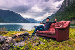 July 21, 2015: Traveller relaxing in a red couch in the norwegian countryside, Norway. July 21, 2015: A Traveller relaxing in a red couch in the norwegian royalty free stock photos