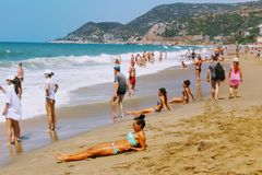 July, 2017 - Vacationers bathe in the sea and sunbathe in the sun on Cleopatra Beach Alanya, Turkey.  Royalty Free Stock Images