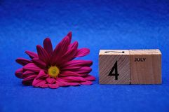 4 July on wooden blocks with a purple daisy. On a blue background stock images
